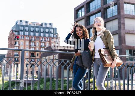 Friends walking on bridge, talking, having fun - Stock Photo