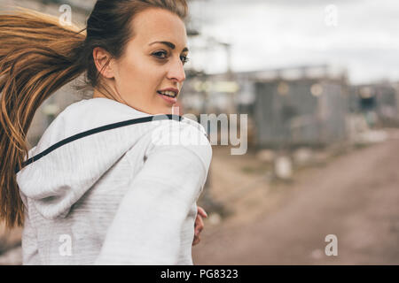 Sportive young woman running outdoors - Stock Photo