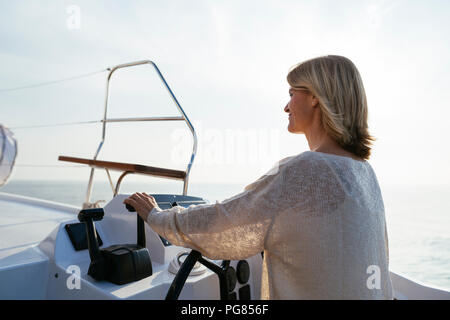Mature woman navigating catamaran on a sailing trip - Stock Photo
