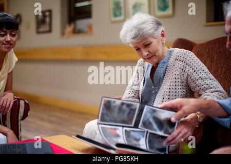 Seniors at retirement home looking at photo albums - Stock Photo