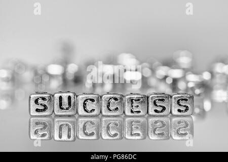 Success word written on grunge silver cube  with black and white bokeh background - Stock Photo