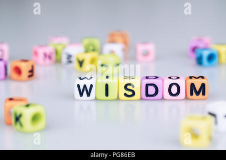 Wisdom word text written on colorful cube with bokeh cube word block background - Stock Photo