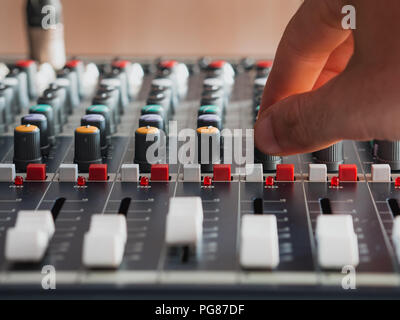 Adjusting buttons on audio mixer in music studio close up - Stock Photo