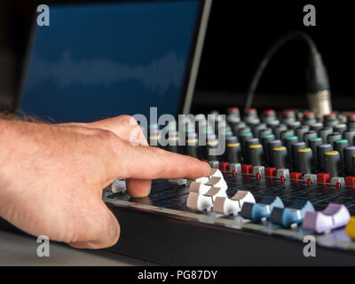 Man adjusting sound on audio mixer in radio station - Stock Photo