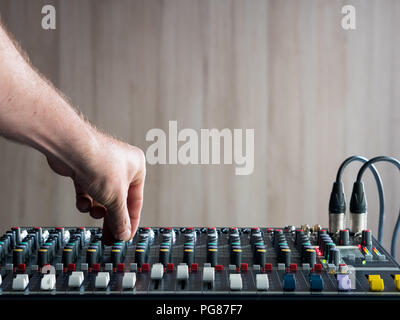Mans hand adjusting buttons on audio mixer in music studio - Stock Photo