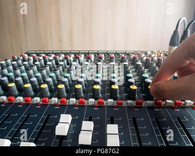 Producing music in studio on audio console mixer - Stock Photo