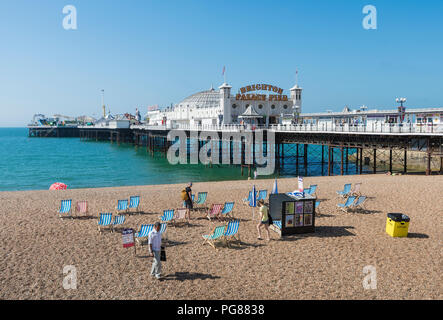 Brighton Palace Pier, a British seaside pier and shingle beach in Summer in Brighton, East Sussex, England, UK. Brighton pier blue sky. - Stock Photo
