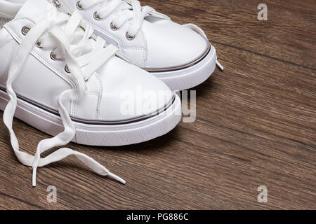 White sneakers on dark wooden surface. Shoes for women in sport fashion style. Copy space - Stock Photo