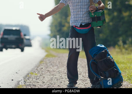 A man in a plaid shirt, dark pants, with an accordion on his shoulders standing by the road and honking, backpack lying at his feet - Stock Photo