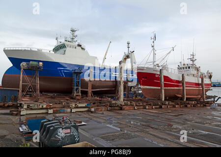 Two fishing trawlers, the Helga Maria, and the Sigurdur Olafsson, being worked on in dry dock in the marina at Reykjavik in Iceland. - Stock Photo