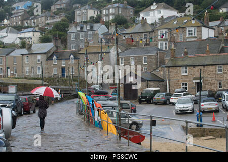 Mousehole, Cornwall, UK. 24th August 2018. UK Weather. It was Yo-yo weather this morning with alternating bright sunshine then heavy downpours at Moushehole, which is a popular bank holiday destination from people around the UK and Europe. Credit: Simon Maycock/Alamy Live News - Stock Photo
