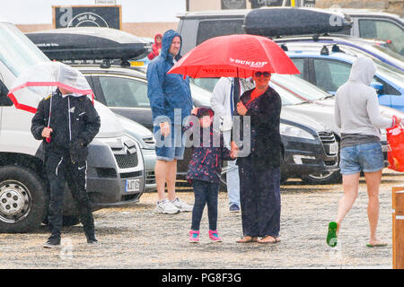 West Bay, Dorset, UK.  24th August 2018. UK Weather.  Holidaymakers sheltering under umbrellas at the seaside resort of West Bay in Dorset look for cover as a rain shower sweeps in.  Picture Credit: Graham Hunt/Alamy Live News - Stock Photo