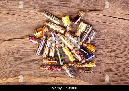 Various kinds of tea and healing herbs in clear glass bottles on - Stock Photo