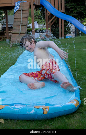 boy on water slide, Neuenkleusheim, Olpe, North Rhine-Westphalia, Germany - Stock Photo