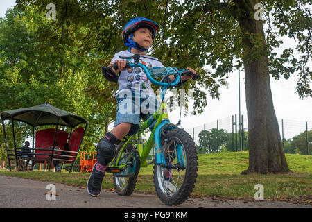 A young boy rides his bicycle in Prospect Park in Reading, UK. He is wearing a bicycle helmet and protective knee and elbow pads. - Stock Photo