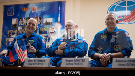 Expedition 55 prime crew members Ricky Arnold of NASA, left, Oleg Artemyev of Roscosmos, center, and Drew Feustel of NASA, right, are seen in quarantine, behind glass, during a press conference, Tuesday, March 20, 2018 at the Cosmonaut Hotel in Baikonur, Kazakhstan. Expedition 55 Soyuz Commander Oleg Artemyev of Roscosmos, Ricky Arnold and Drew Feustel of NASA are scheduled to launch to the International Space Station aboard the Soyuz MS-08 spacecraft on Wednesday, March, 21. - Stock Photo