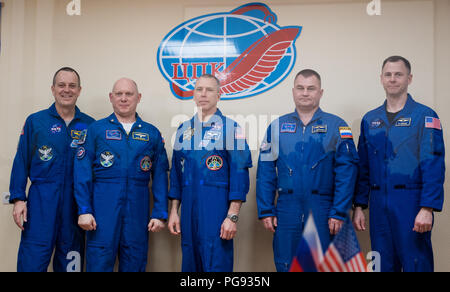 Expedition 55 prime crew members Ricky Arnold of NASA, left, Oleg Artemyev of Roscosmos, second from left, and Drew Feustel of NASA, center, pose for a picture with backup crew members Alexey Ovchinin of Roscosmos, second from right, and Nick Hague of NASA, right, at the conclusion of a press conference, Tuesday, March 20, 2018 at the Cosmonaut Hotel in Baikonur, Kazakhstan. Arnold, Artemyev, and Feustel are scheduled to launch to the International Space Station aboard the Soyuz MS-08 spacecraft on Wednesday, March, 21. - Stock Photo