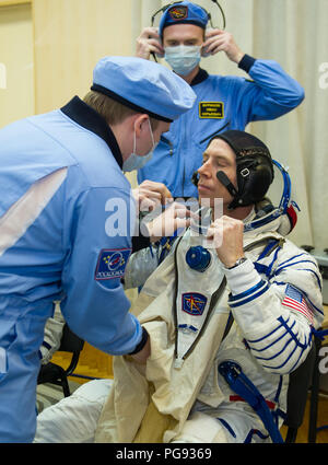 Expedition 55 flight engineer Drew Feustel of NASA is helped into his Russian Sokol suit as he and fellow crewmates, Soyuz Commander Oleg Artemyev of Roscosmos and Ricky Arnold of NASA prepare for their Soyuz launch to the International Space Station Wednesday, March 21, 2018 in Baikonur, Kazakhstan.  Feustel, Artemyev, and Arnold launched aboard the Soyuz MS-08 spacecraft at 1:44 p.m. Eastern time (11:44 p.m. Baikonur time) on March 21 to begin their journey to the International Space Station. - Stock Photo