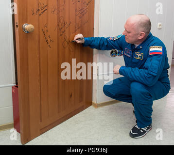 Expedition 55 Soyuz Commander Oleg Artemyev of Roscosmos performs the traditional door signing at the Cosmonaut Hotel prior to departing the hotel for launch on a Soyuz rocket with fellow crewmates Ricky Arnold and Drew Feustel of NASA, Wednesday, March 21, 2018 in Baikonur, Kazakhstan.  Artemyev, Arnold, and Feustel will launch in their Soyuz MS-08 spacecraft to the International Space Station to being a five month mission. - Stock Photo