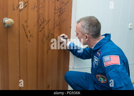 Expedition 55 flight engineer Drew Feustel of NASA performs the traditional door signing at the Cosmonaut Hotel prior to departing the hotel for launch on a Soyuz rocket with fellow crewmates Oleg Artemyev of Roscosmos and Ricky Arnold of NASA, Wednesday, March 21, 2018 in Baikonur, Kazakhstan.  Feustel, Artemyev, and Arnold will launch in their Soyuz MS-08 spacecraft to the International Space Station to being a five month mission. - Stock Photo