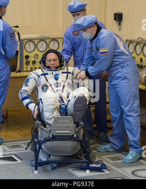Expedition 55 Soyuz Commander Oleg Artemyev of Roscosmos prepares to have his Russian Sokol suit pressure checked in preparation for launch aboard the Soyuz MS-08 spacecraft, Wednesday, March 21, 2018 at the Baikonur Cosmodrome in Kazakhstan. Artemyev and flight engineers Ricky Arnold and Drew Feustel of NASA launched aboard the Soyuz MS-08 spacecraft at 1:44 p.m. Eastern time (11:44 p.m. Baikonur time) on March 21 to begin their journey to the International Space Station. - Stock Photo