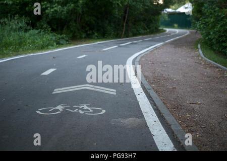 Photo of bicycle road among trees - Stock Photo