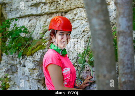 Portrait of smiling sports woman in red helmet looking at camera next to mountain - Stock Photo
