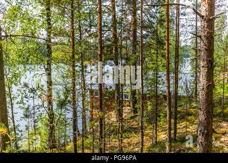 A typical red boat house  on the shore of the Saimaa lake in Finland - 9 - Stock Photo