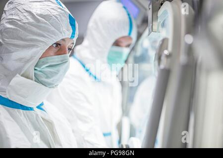 Technicians working in sealed, sterile isolator units in a laboratory that manufactures human tissues for implant. Such tissues include bone and skin grafts. - Stock Photo