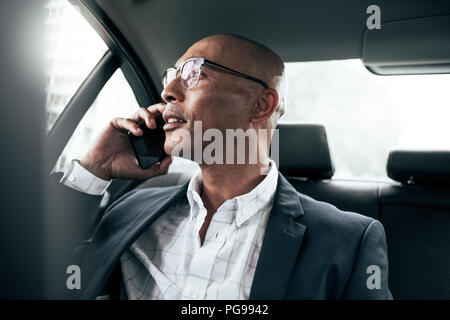 Businessman wearing eyeglasses talking over cell phone sitting in his sedan looking out the window. Man managing business on mobile phone sitting in c - Stock Photo