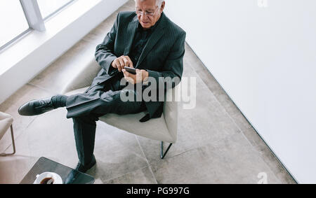 High angle view of senior businessman texting with mobile phone. Mature corporate professional reading emails on his smartphone during break. Senior m - Stock Photo