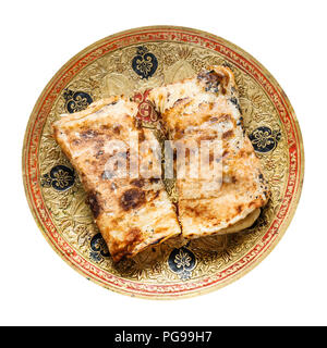 Indian cuisine - rolled Butter Naan flat bread baked in tandoor with butter on brass plate isolated on white background - Stock Photo