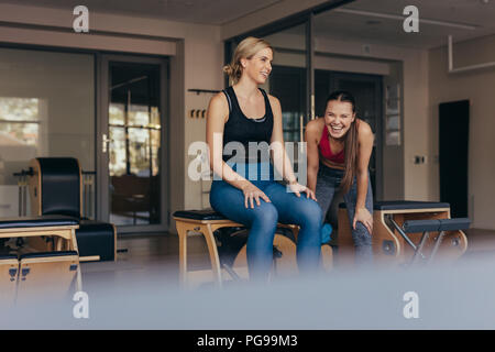 Women sitting on a bench in gym relaxing while her trainer is laughing. Women doing pilates workout at the gym. - Stock Photo