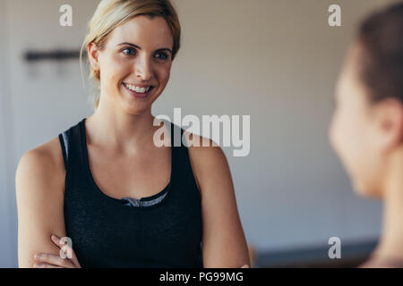 Smiling woman in fitness wear at a pilates training gym. Woman talking to a friend at the gym. - Stock Photo