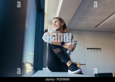 Smiling fitness woman holding water bottle sitting in a pilates gym. Woman relaxing after workout looking out of a window in a pilates gym. - Stock Photo