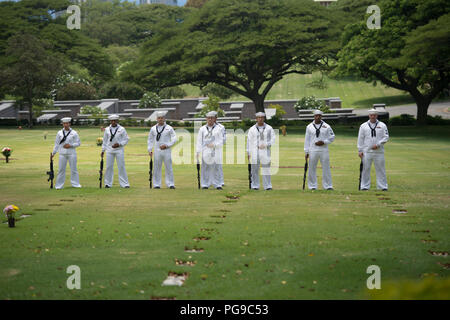 U.S. Navy honor guardsmen assigned to Navy Region Hawaii stand at parade rest during the funeral of Machinist's Mate 1st Class Arthur Glenn at the National Memorial Cemetery of the Pacific, Honolulu, Hawaii, Aug. 21, 2018. On Dec. 7, 1941, Glenn was assigned to the USS Oklahoma which sustained fire from Japanese aircraft. The ship capsized after multiple torpedo hits, resulting in the deaths of more than 429 crew members at Ford Island, Pearl Harbor. Glenn is the 100th Oklahoma sailor identified through DNA analysis with the help of the Defense POW/MIA Accounting Agency (DPAA) and returned to  - Stock Photo