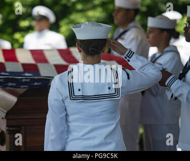 A U.S. Navy honor guardsman assigned to Navy Region Hawaii salutes the casket of Machinist's Mate 1st Class Arthur Glenn at the National Memorial Cemetery of the Pacific, Honolulu, Hawaii, Aug. 21, 2018. On Dec. 7, 1941, Glenn was assigned to the USS Oklahoma which sustained fire from Japanese aircraft. The ship capsized after multiple torpedo hits, resulting in the deaths of more than 429 crew members at Ford Island, Pearl Harbor. Glenn is the 100th Oklahoma sailor identified through DNA analysis with the help of the Defense POW/MIA Accounting Agency (DPAA) and returned to his family for buri - Stock Photo