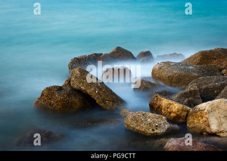 Beautiful composition of rocks and spindrift at a beach in Greece photographed during golden hour - Stock Photo