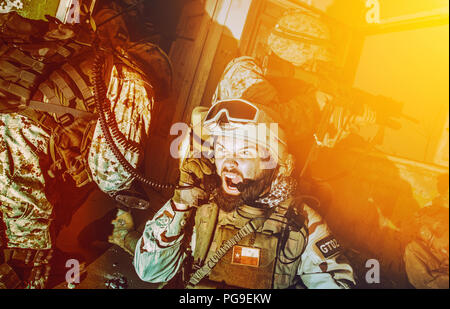 Army team leader coordinating teammates with radio - Stock Photo