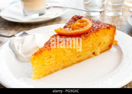 A piece of traditional greek orange cake with sour cream on white plate. - Stock Photo