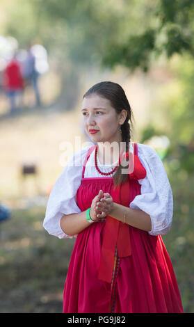 Beautiful young Russian girl in national dress with a ribbon in the queue for the Slavic feast of Apple gathering - Stock Photo