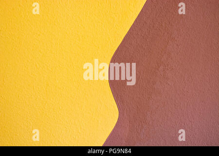 A fragment of a wall plastered in two colors, yellow and brown, for use as a background. - Stock Photo