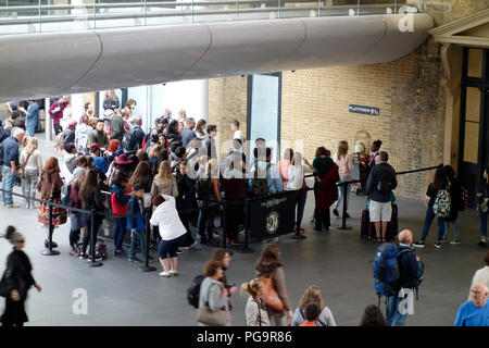 Young people queuing up at Plaform 9 and 3/4 to have their selfie taken - Stock Photo
