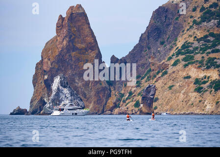 View of the sea, rocks and a floating man but a surfboard near the yacht - Stock Photo