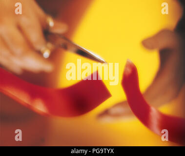 A hand with scissors cutting a red ribbon. - Stock Photo