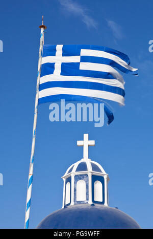 A blue and white church top with cross and an equally colored greek flag with blue sky. - Stock Photo