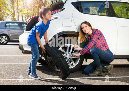 Happy mother and son changing flat tire together - Stock Photo
