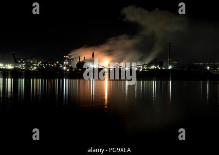 Oil refinery factory processing chemicals in the night. Air pollution and global warming on the rise. - Stock Photo