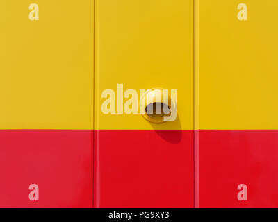 New yellow and red metal panel wall of building with round ventilation hole - Stock Photo