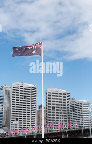 Australian flag flying at Darling Harbour with city behind, and pink banners on Pyrmont Bridge New South Wales, Australia - Stock Photo
